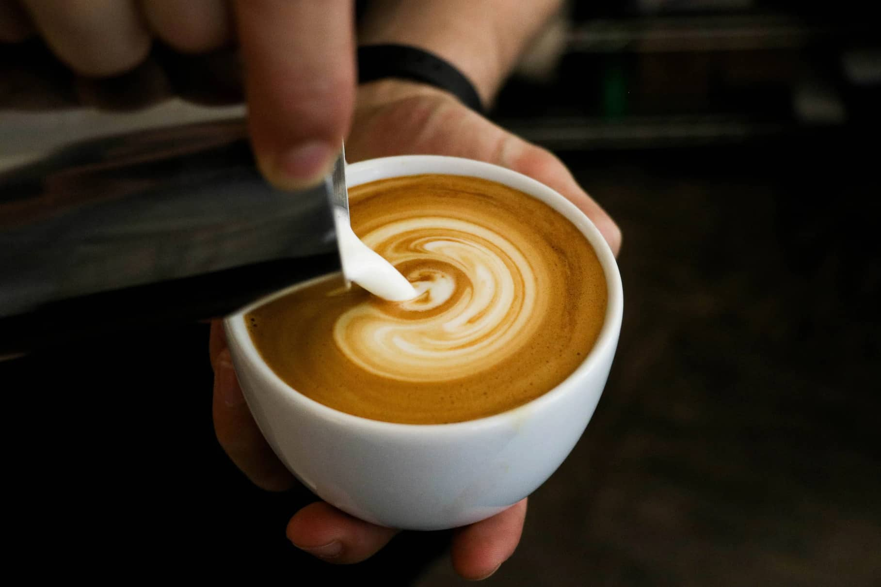 a close up of a cappuccino being poured
