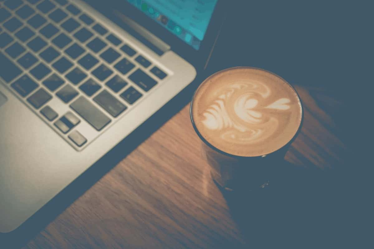 Overhead shot of a latte next to a laptop
