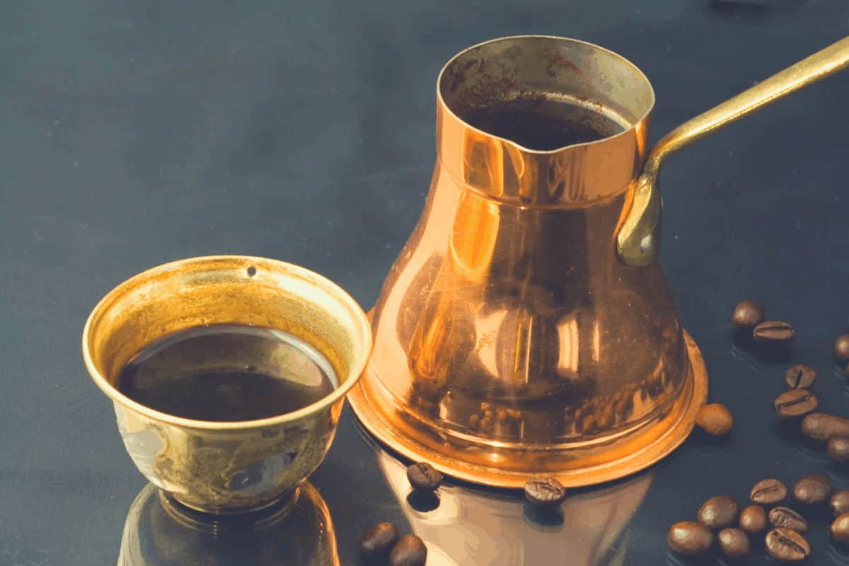 A photo of a brass cezve and serving cup