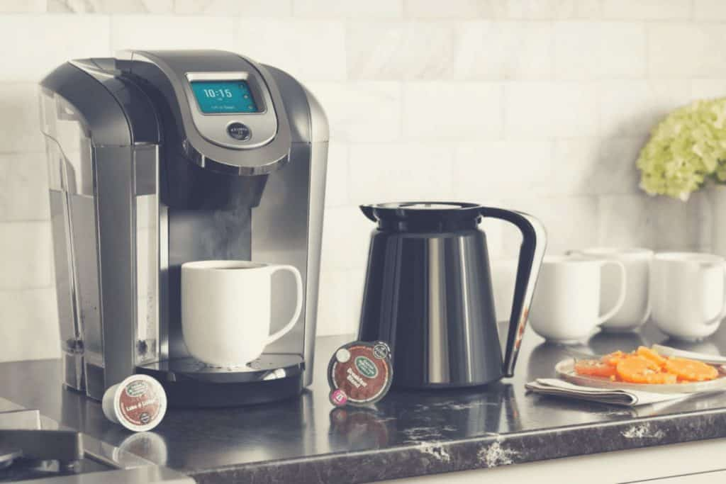 A promotional shot of the Keurig K475 with carafe and pods