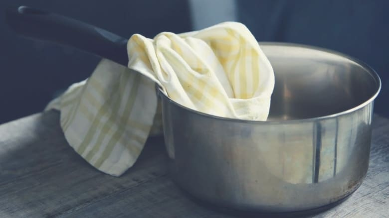 a saucepan with a cleaning cloth inside it