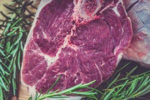Uncooked beef on a bed of fresh rosemary