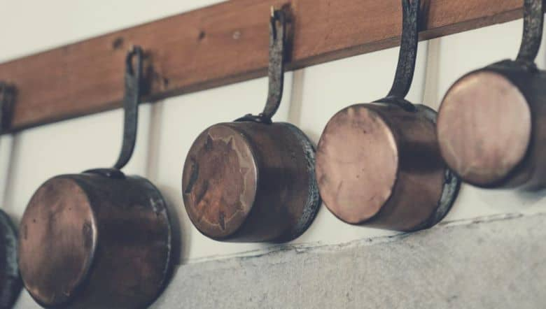 copper pots and pans hanging from a rack