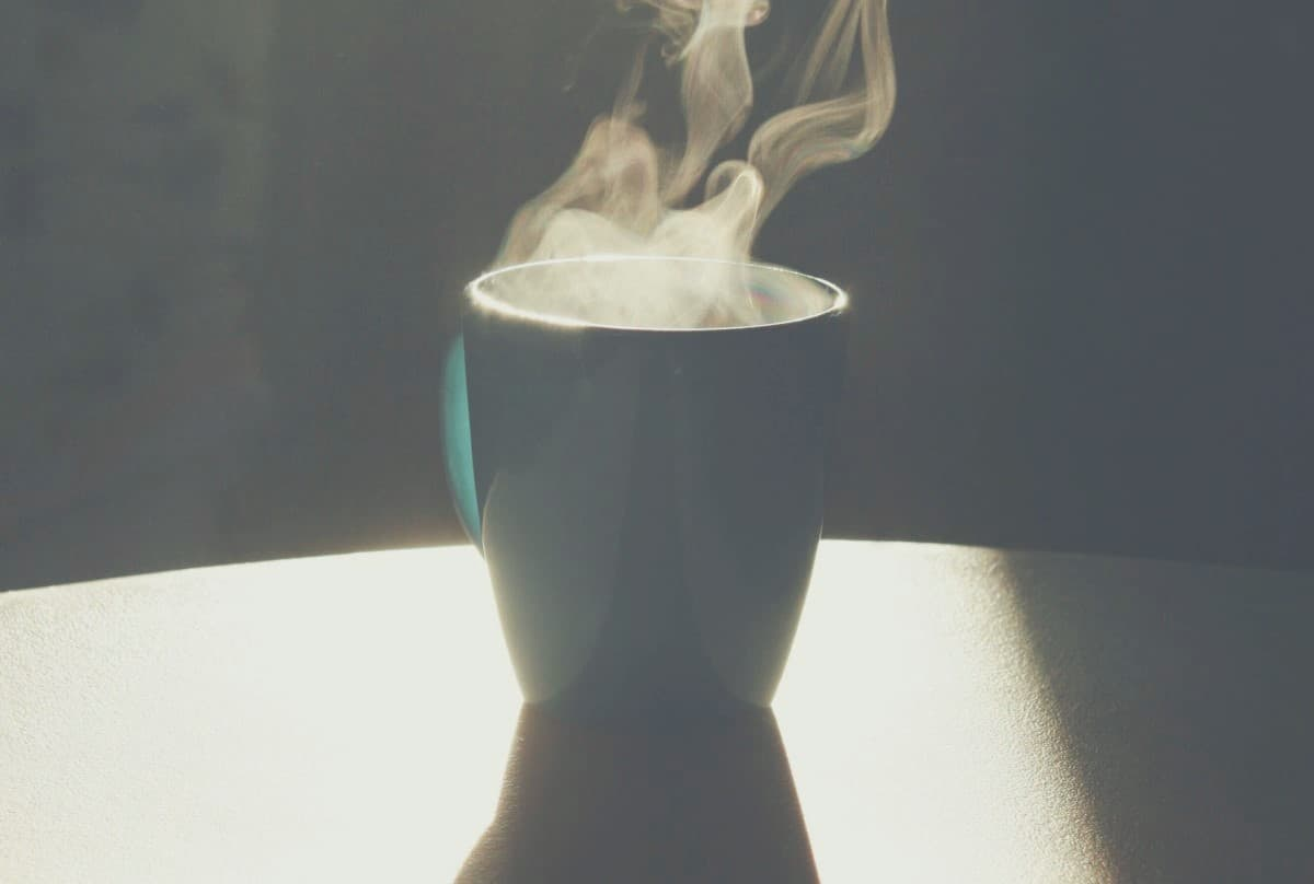 A steaming hot cup of coffee sitting on a table