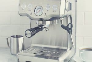 The Breville Infuser with a milk frothing jug and cup of coffee nearby