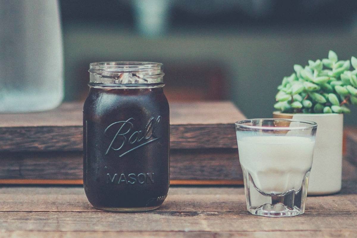a glass of milk next to a mason jar filled with cold brew coffee