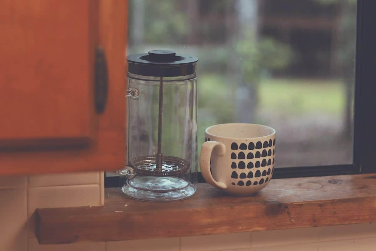 A French Press and a cup sitting on a windowsill
