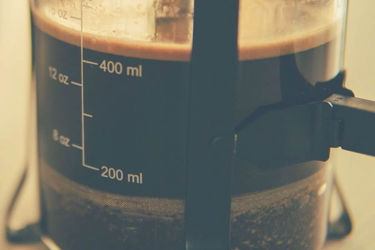 An extreme close up of a coffee plunger in a French Press