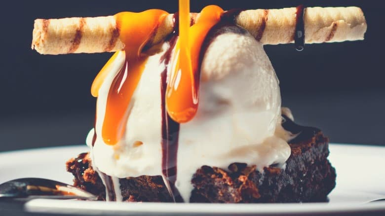 A close up of a sticky brownie pudding with cream and caramel sauce