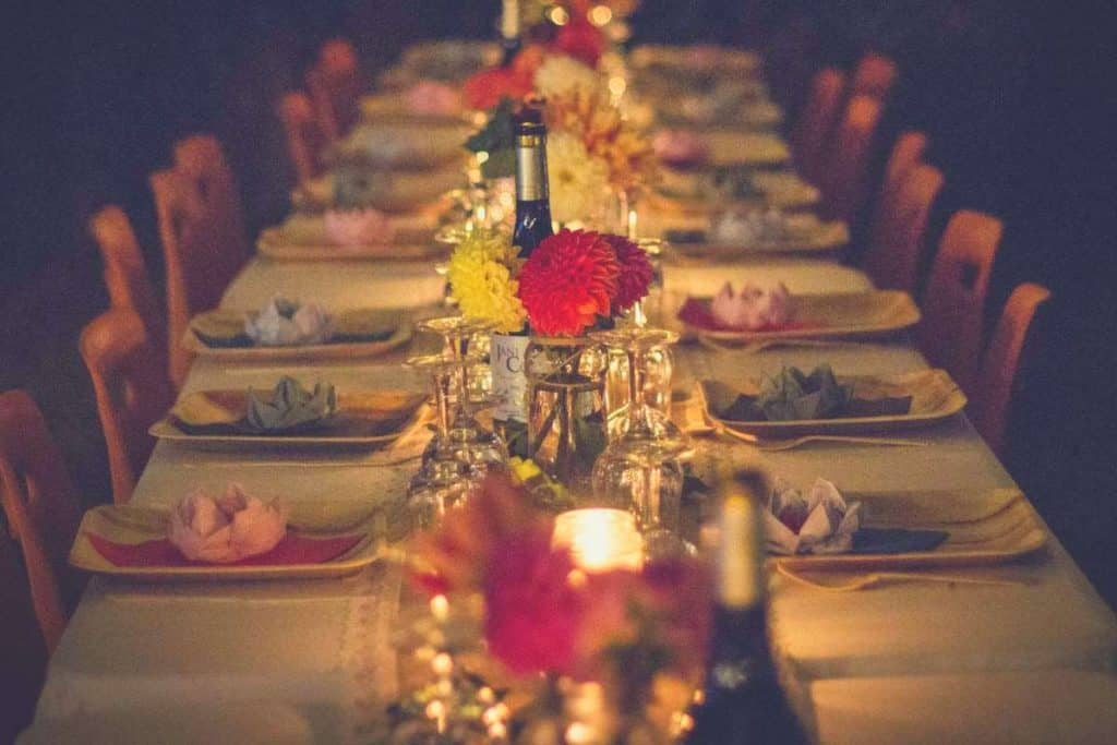 a shot of a long dining table with a bottle centrepiece