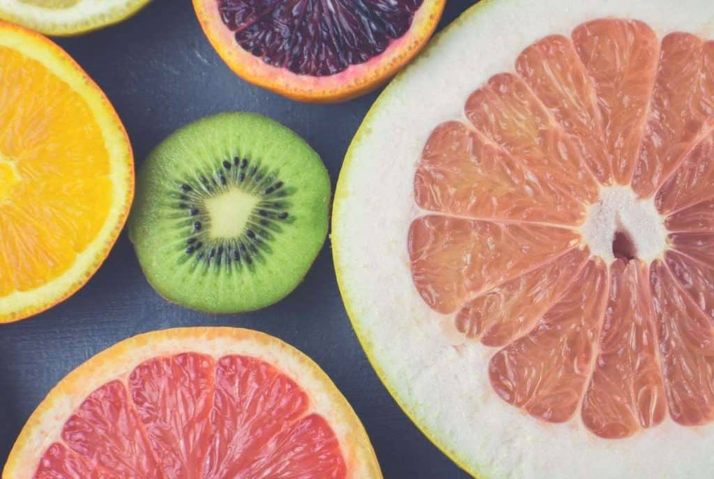 A close up shot of grapefruit, lemon and kiwi fruit on a chopping board