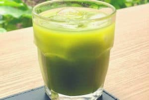 A green juice drink on a wooden table on a garden bench