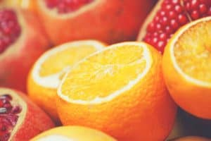 A close up shot of many oranges and pomegranates