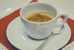 A cup of espresso on a saucer with a teaspoon