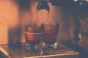Two shots of espresso being brewed into glasses by an espresso machine