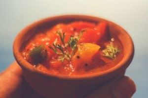 A tomato salsa dip in a brown ceramic pot