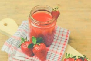 A strawberry smoothie on a cutting board with fresh strawberries around it
