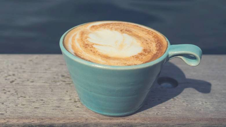 Cappuccino in a blue cup on a wooden bench