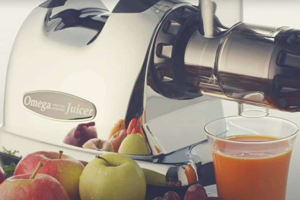 An Omega cold press juicer with a glass of juice and various fruits and vegetables