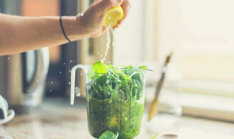 A lemon being squeezed into a blender jar while making a mojito