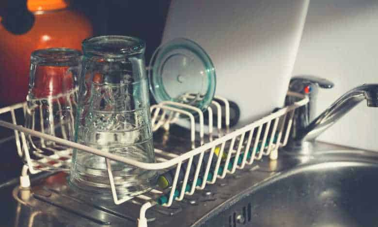 A dishwashing rack on a sink, with glass on it, next to a tap