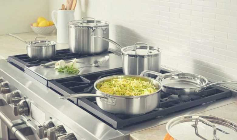 Many items of the Cuisinart MultiClad Pro cookware set on a home kitchen oven hob