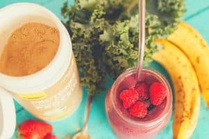 strawberries, kale, bananas and protein powder combined into a protein shake