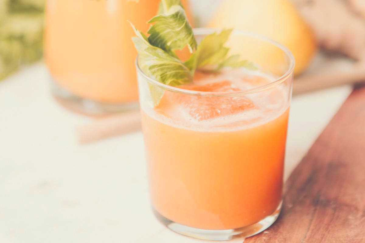 A glass of carrot juice with a carrot stalk sitting on top