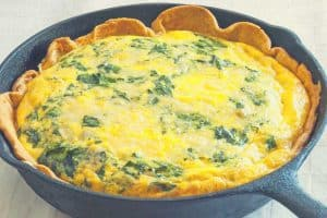 A pastry dish in a cast iron skillet with a creamy vegetable filling